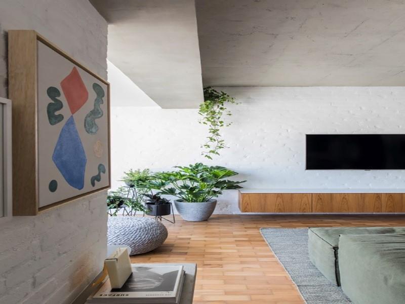 Despojado e minimalista, apê mistura concreto, madeira e metal